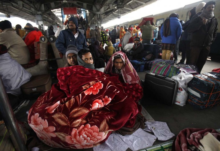 Passengers wrap themselves in a blanket as they wait to board a train on a cold winter morning in New Delhi January 7, 2013. The current cold weather in northern India has killed more than 100 homeless people, an aid group said last week. Temperatures in New Delhi have dipped to 2.4 degrees Celsius (36.32 degrees Fahrenheit), according to information posted on India's meteorological department website. (Mansi Thapliyal/Reuters)