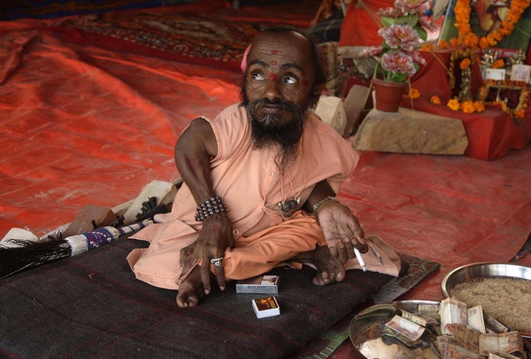 """Mahadev Bharti, 56, a Sadhu or a Hindu holy man who claims to stand at 18-inch (46 cm), rests inside a tent on the banks of the river Ganges during the ongoing """"Kumbh Mela"""", or Pitcher Festival, in the northern Indian city of Allahabad January 28, 2013. During the festival, Hindus take part in a religious gathering on the banks of the river Ganges. """"Kumbh Mela"""" will return to Allahabad in 12 years. (Jitendra Prakash/Reuters)"""
