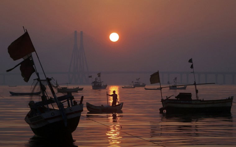A fisherman anchors his boat in the low tide sand as the sun sets in Mumbai. (Vivek Prakash/Reuters)