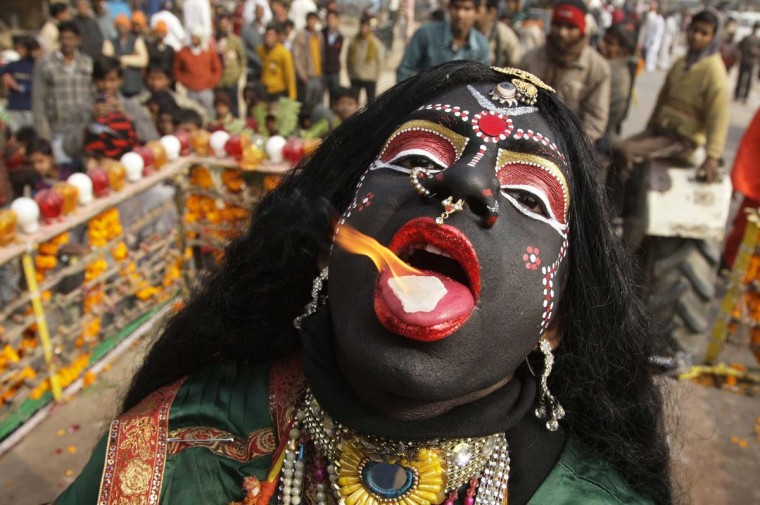 """A man dressed as Hindu goddess Kali, the goddess of power, performs with a burning camphor tablet on his tongue during a religious procession ahead of the """"Kumbh Mela"""" or Pitcher Festival, in the northern Indian city of Allahabad January 6, 2013. (Jitendra Prakash /Reuters)"""