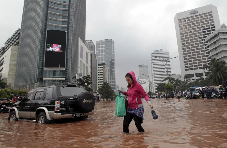 A woman crosses a flooded area at the business district in Jakarta . Heavy monsoon rains triggered severe flooding in large swathes of the Indonesian capital Jakarta with many government offices and businesses forced to closed because staff could not get to work. (Supri/Reuters photo)
