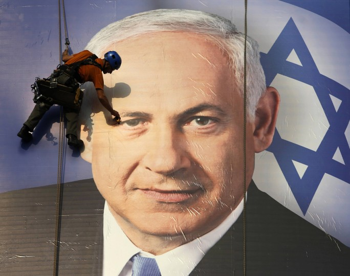 A worker installs a banner depicting Israel's Prime Minister Benjamin Netanyahu in Tel Aviv. Netanyahu looks set to form a new governing coalition after next week's election, polls show, with the only question being whether he wants to soften its hardline contours. (Baz Ratner/Reuters photo)