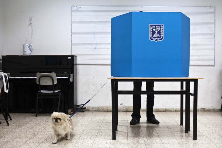 A man stands behind a voting booth with a dog as he picks his ballot for the parliamentary election in a polling station in Tel Aviv January 22, 2013. Israelis voted on Tuesday in an election that is expected to hand hawkish Prime Minister Benjamin Netanyahu a third term, opening the way for a showdown with Iran and bolstering opponents of Palestinian statehood. (Nir Elias/Reuters)