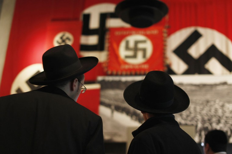 Ultra-Orthodox Jewish visitors look at a display of Nazi flags at Yad Vashem's Holocaust History Museum in Jerusalem ahead of International Holocaust Remembrance day which will be marked on January 27. (Amir Cohen/Reuters)