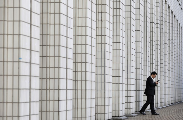 A man walks out from a business building in Tokyo. Sentiment among Japanese manufacturers improved for a second straight month and is expected to turn into a positive reading in the coming few months, a Reuters poll showed, providing some evidence that the economy is crawling out of a mild recession. (Toru Hanai/Reuters)