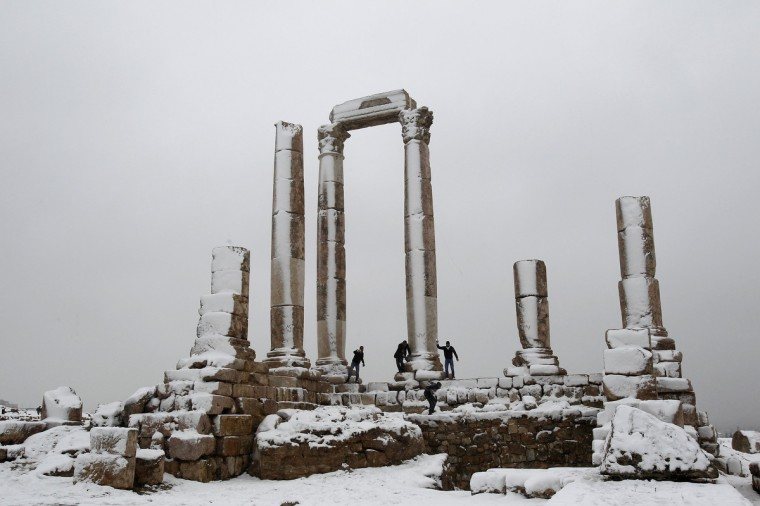 Men play with snow after a heavy snowstorm in Amman citadel. Snowstorms and heavy rain have caused the closure of main streets in the capital Amman and other cities over the past two days. (Ali Jarekji/Reuters photo)