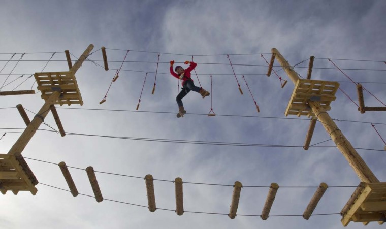 A woman climbs during the opening of the rope park at the Shimbulak Ski Resort in the Tien Shan mountains outside Almaty January 22, 2013. The newly opened park is world's highest rope park mounted on artificial supports, said its designers. (Shamil Zhumatov/Reuters)