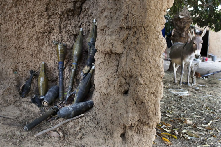 Rocket-propelled grenades believed to belong to Islamist rebels are stockpiled next to a donkey in a courtyard in Diabaly. (Joe Penney/Reuters)