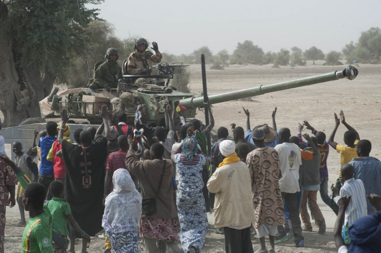French troops aboard a tank are greeted by the population as they arrive in Timbuktu. French and Malian troops retook control of Timbuktu, a UNESCO World Heritage site, after Islamist rebel occupiers fled the ancient Sahara trading town and torched several buildings, including a library holding priceless manuscripts. (Arnaud Roine/Reuters)