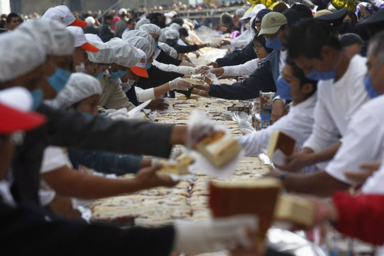 "People receive the pastry ""Roscon de reyes"" (literally, kings' ring) to eat during a Kings' Day celebration, at Zocalo Square in Mexico City. The bread, measuring 1,900 meters (6,233 ft), is a typical dessert made on the morning of the Christian holiday of Epiphany, the date when the three Wise Men visited the baby Jesus. It was divided into some 200,000 pieces for free sampling, according to local media. (Edgard Garrido/Reuters)"