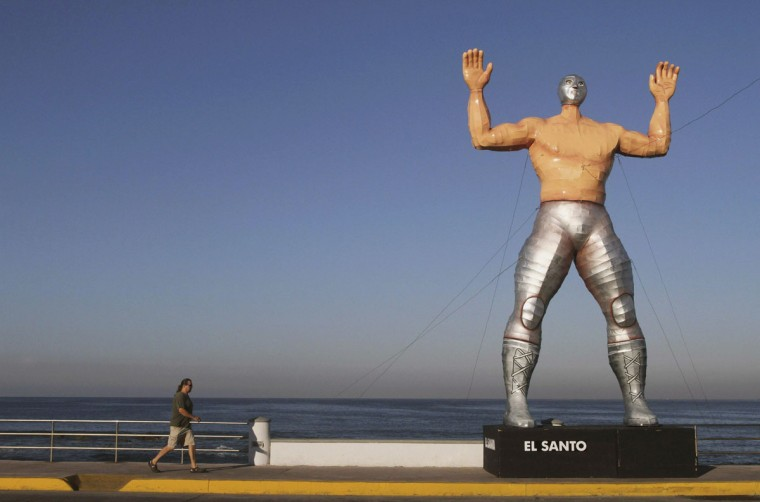 A person walks past a giant figure of famous Lucha Libre wrestler El Santo in Mazatlan January 24, 2013. The municipality set up eight giant figures made by Mexican artist Jorge Gonzalez Neri for the upcoming carnival celebrations. (Stringer/Reuters)