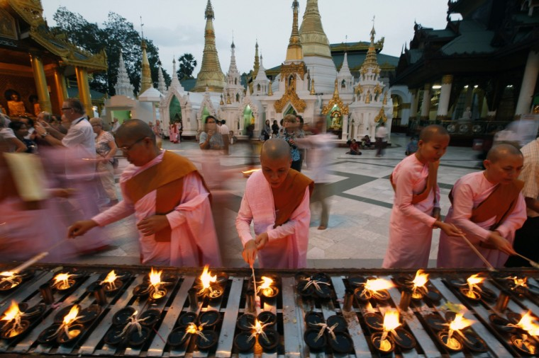 Nuns light candles at Shwe Dagon pagoda in Yangon. (Minzayar/Reuters)