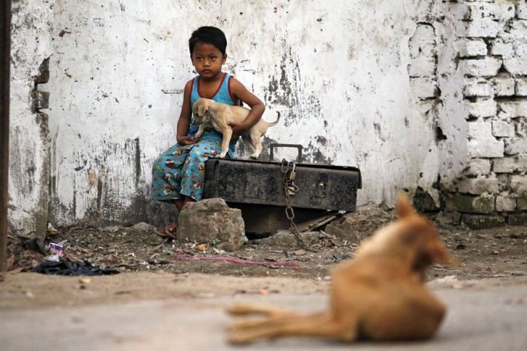 A boy sits as he holds a puppy on a street side in Yangon, Myanmar. (Soe Zeya Tun/Reuters)