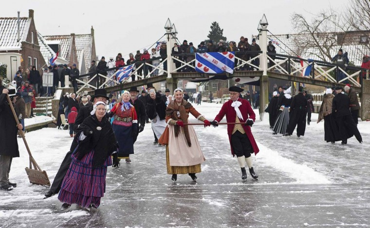 Skaters dressed in traditional Dutch costumes skate on the canal in Hindeloopen January 26, 2013. When the canals and lakes freeze, the Dutch get out their skates and venture out on the ice. In Friesland, skaters dressed in traditional costumes gather for a day of ice skating, pole-sledding, and other entertainment on ice. The skaters wear an old-fashioned form of skate with special blades to help them glide across the ice without tiring, and usually skate together in couples or groups; this type of skating can be seen in many old Dutch paintings and is particularly popular with older people. (Michael Kooren/Reuters)