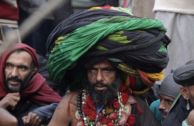 A devotee wears a big turban made from colorful sheets of cloth as he sits outside the shrine of Muslim Sufi Saint Data Ganj Bakhsh on his death anniversary in Lahore January 2, 2013. Devotees started a three-day celebration of the 969th festival of Hazrat Ali Bin Usman popularly known as Data Gunj Bakhsh. (Mohsin Raza/Reuters)