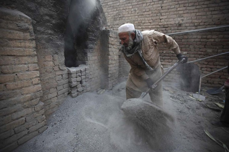 Uais Khan, 62, shovels sand and salt into an oven at a factory in Rawalpindi January 28, 2013. Heated sand and salt are later used to cook corn overnight, before the corn are sold as a popular street food dish. (Mian Khursheed/Pakistan)