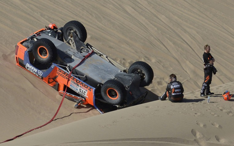 Robby Gordon (L) of the U.S. and co-pilot Kellon Walch are seen near their Hummer after they crashed during the 4th stage of the Dakar Rally 2013 from Nazca to Arequipa, January 8, 2013. (Franck Fife/Getty Images)