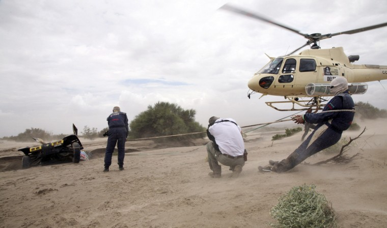 France's Pascal Thomasse, co-pilot Pascal Larroque and Dakar director Etienne Lavigne (C) are helped by a helicopter to take out their Buggy MD Rallye which was stuck in a river following a flash flood during the 11th stage of the Dakar Rally 2013 from La Rioja to Fiambala, January 16, 2013. (Reuters)
