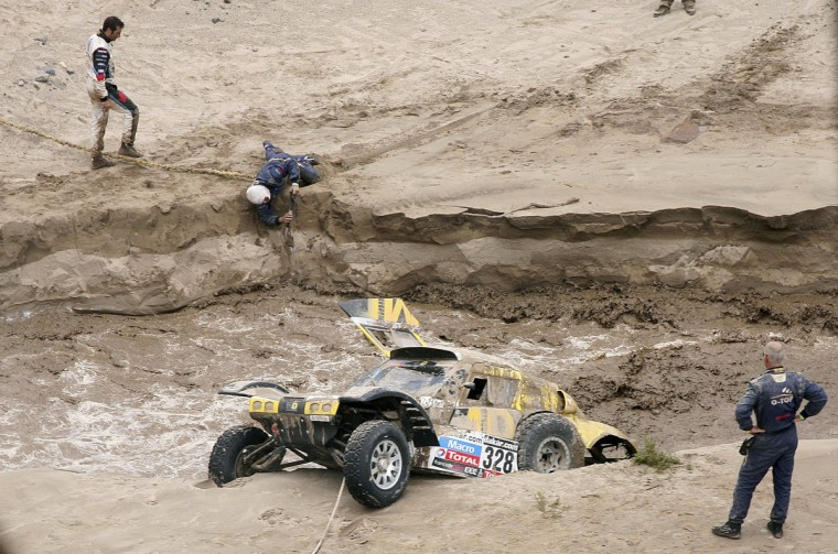France's Pascal Thomasse and co-pilot Pascal Larroque are stuck in a river with their Buggy MD Rallye following a flash flood during the 11th stage of the Dakar Rally 2013 from La Rioja to Fiambala, January 16, 2013. (Reuters)
