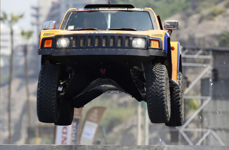 Robby Gordon and co-pilot Kellon Walch of the U.S. jump from the podium in their Hummer during the departure ceremony of the fifth South American edition of the Dakar Rally 2013 in Lima January 5, 2013. (Janine Costa/Reuters)