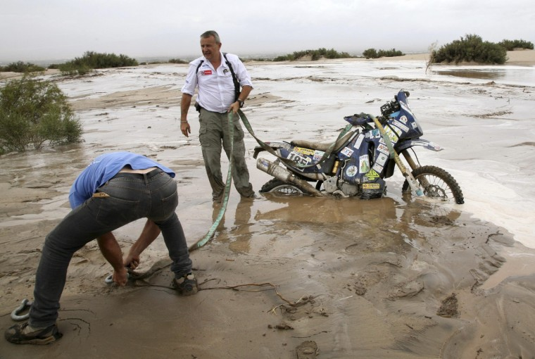 Dakar director Etienne Lavigne helps to remove a motorbike stuck in a river following a flash flood during the 11th stage of the Dakar Rally 2013 from La Rioja to Fiambala January 16, 2013. (Reuters)