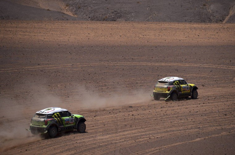 France's Stephane Peterhansel and co-pilot Jean-Paul Cottret and Spain's Nani Joan Roma and co-pilot France's Michel Perin compete with their Mini during the 13th stage of the Dakar Rally 2013 from Copiapo to La Serena, January 18, 2013. (Reuters)