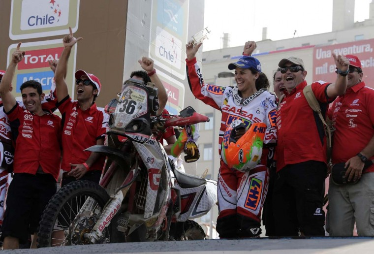Spain's Laia Sanz (3rd R) celebrates with her mechanics on the podium of the fifth South American edition of the Dakar rally 2013 in Santiago January 20, 2013. (Jacky Naegelen/Reuters)
