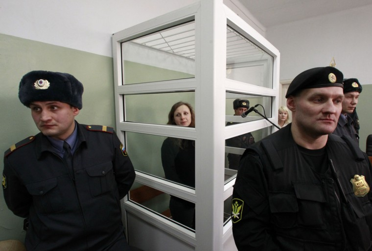 "A member of the female punk band ""Pussy Riot"" Maria Alyokhina looks out from a defendants' box during a court hearing in Berezniki in Perm region, near the Ural mountains. According to local media, the Berezniki City Court is expected to hear her motion to postpone carrying out the rest of her sentence because of her young child at home, local media reported. Alyokhina is serving a sentence for staging an anti-Kremlin protest on the altar of Moscow's main Russian Orthodox church. (Sergei Karpukhin/Reuters)"