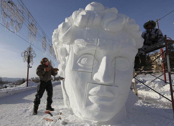 "Alexei Vasyukov (L) and Mikhail Rukosuev, members of a team from the Russian Ural city of Perm, work on a snow sculpture based on a creation by Italian Renaissance artist Michelangelo during the 1st International festival of snow and ice sculptures called ""The Magical Ice of Siberia"" on an embankment of the Yenisei River in Krasnoyarsk, January 17, 2013. Ice and snow sculptors representing USA, China, Kazakhstan and 25 Russian cities take part in a five-day-long competition which will start next Monday, according to the festival organizers. (Ilya Naymushin /Reuters)"