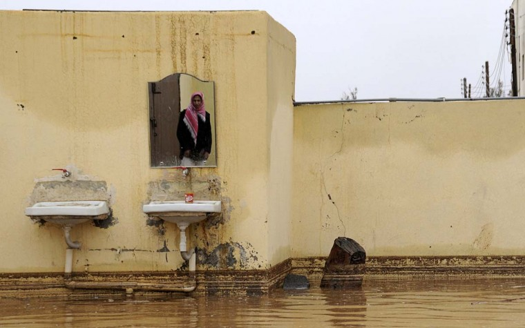 A Saudi man is reflected in a mirror in his flooded home after heavy rain in Tabuk, 1500 km (932 miles) from Riyadh January 28, 2013. (Mohamed Alhwaity/Reuters)
