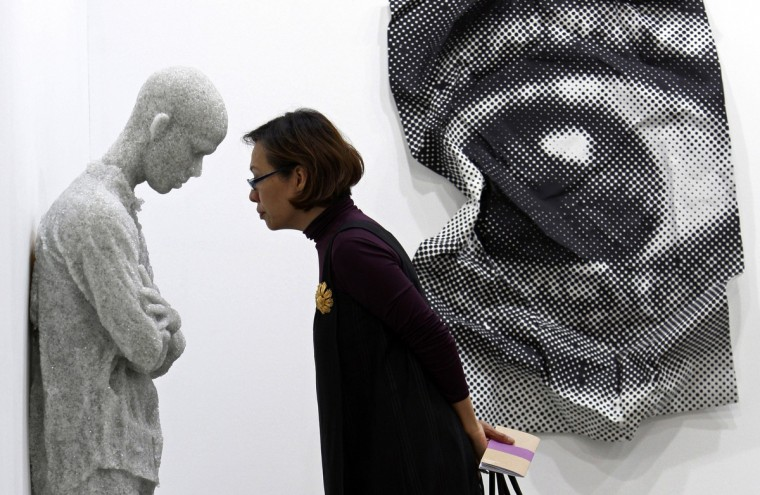"""A visitor looks at """"Figure with Arms Crossed"""" (L) by Daniel Arsham of the U.S. next to """"Inside Out sculpture #2"""" by French artist J.R. during media preview at Art Stage Singapore in Marina Bay Sands Convention and Exhibition center in Singapore. (Edgar Su/Reuters)"""