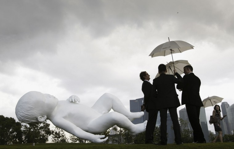 Visitors carrying umbrellas look at the newly unveiled creation of British artist Marc Quinn, a 9m (30 feet) long painted bronze sculpture entitled 'Planet' at Gardens by the Bay in Singapore. (Edgar Su/Reuters)