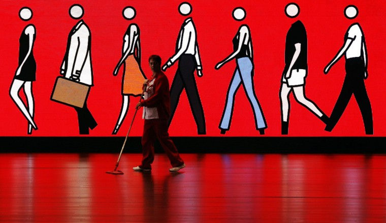 A cleaner sweeps the floor as she walks past an illuminated sign depicting people walking, at Spain's Santander headquarters in Boadilla del Monte outside Madrid. Santander, the largest lender in the euro zone, has sharply raised provisions against bad loans after defaults rose in its home market and key earnings-driver Brazil, while writedowns on rotten Spanish real estate also contributed to a 59 drop in yearly net profit. (Sergio Perez/Reuters)