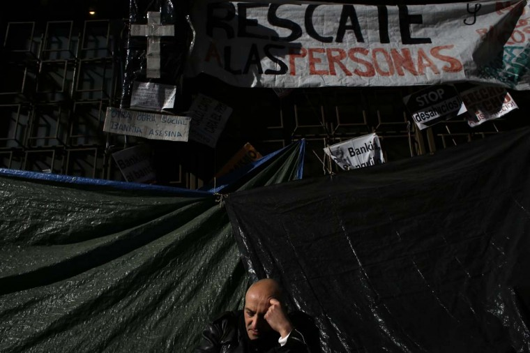 A protester sits outside the headquarters of Spanish nationalised lender Bankia, at a campsite where protesters have demonstrated for some 100 days, in Madrid January 28, 2013. Spain was forced to ask Europe for up to 100 billion euros ($132.9 billion) to help its weakest banks last year and four of the lenders it took over, including Bankia, have to cut thousands of jobs to shrink their balance sheets as a condition of their rescue. (Juan Medina/Reuters)