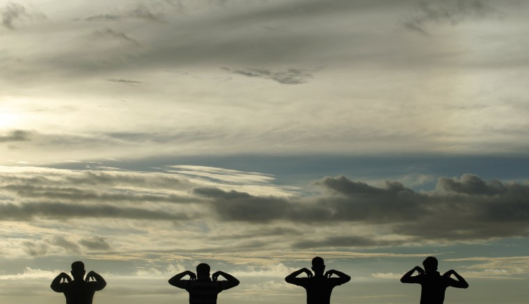 A group of men perform physical exercise training as sun set at Galle Face green in Colombo, Sri Lanka. (Dinuka Liyanawatte/Reuters)