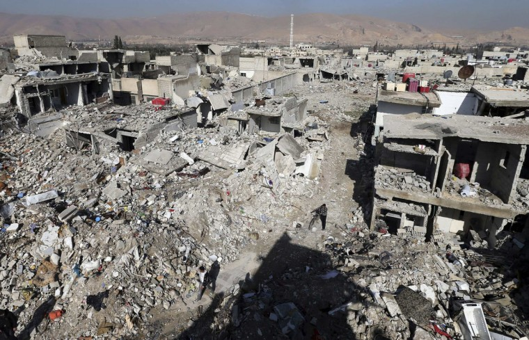 A man passes by buildings destroyed by Syrian air force air strikes in the Duma neighborhood of Damascus January 17, 2013. (Goran Tomasevic/Reuters)