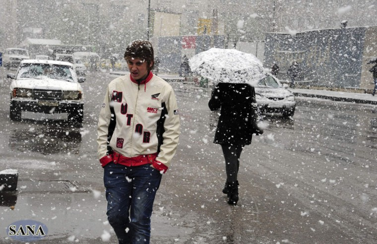 People walk on a street during snowfall in Damascus in this handout photograph released by Syria's national news agency. (SANA/Reuters)