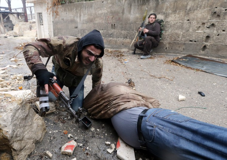 A Free Syrian Army fighter drags his comrade who was shot by sniper fire during heavy fighting in the Ain Tarma neighborhood of Damascus January 30, 2013. The fighter died soon after. (Goran Tomasevic/Reuters)
