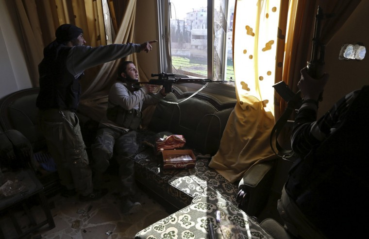 Fighters from the Sadik unit of Free Syrian Army's Tahrir al Sham brigade look at Syrian soldiers' position from inside a house during heavy fighting in Mleha suburb of Damascus January 22, 2013. (Goran Tomasevic/Reuters)