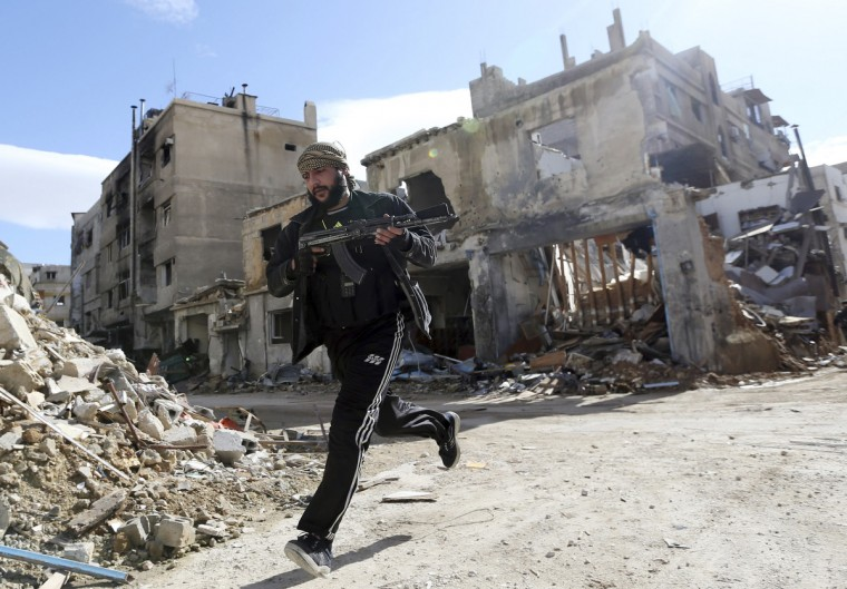 A fighter from Fateh al Sham unit of the Free Syrian Army runs across a street in Haresta neighborhood of Damascus January 20, 2013. (Goran Tomasevic/Reuters)