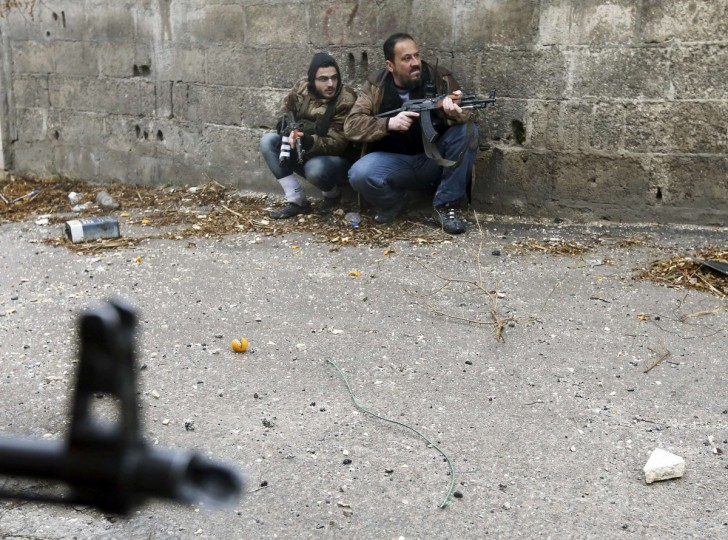 Free Syrian Army fighters take position just before they were hit by Syrian Army sniper fire during heavy fighting in the Ain Tarma neighborhood of Damascus January 30, 2013. The fighter on the right died soon after, while his comrade was wounded. (Goran Tomasevic/Reuters)