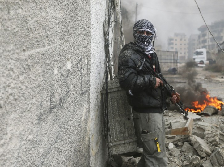 A masked Free Syrian Army fighter smokes during heavy fighting in the Ain Tarma neighborhood of Damascus January 30, 2013. (Goran Tomasevic/Reuters)