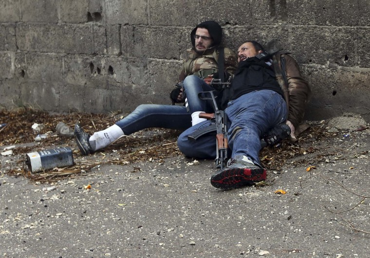 Free Syrian Army fighters lie on the ground as they are shot by sniper fire in the Ain Tarma neighborhood of Damascus January 30, 2013. The fighter on the right dies soon after, while his comrade was wounded. (Goran Tomasevic/Reuters)