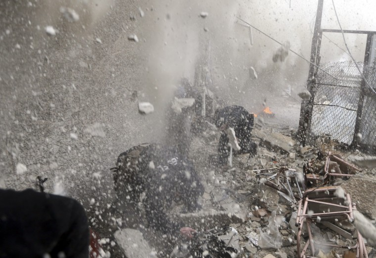 Free Syrian Army fighters run for cover as a tank shell explodes on a wall during heavy fighting in the Ain Tarma neighborhood of Damascus January 30, 2013. (Goran Tomasevic/Reuters)