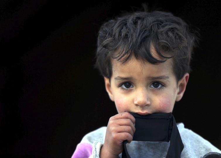 An internally displaced boy looks out of a tent at a village outside Damascus January 29, 2013. (Goran Tomasevic/Reuters)