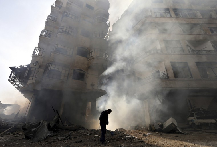 A man walks in front of a burning building after a Syrian Air force air strike in Ain Tarma neighborhood of Damascus January 27, 2013. (Goran Tomasevic/Reuters)