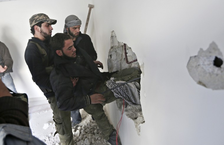 Fighters from the Free Syrian Army's Tahrir al Sham brigade carry a wounded fighter through a hole in a wall during heavy fighting in Mleha suburb of Damascus January 26, 2013. (Goran Tomasevic/Reuters)