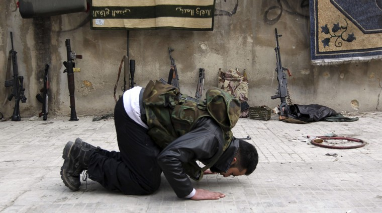 A Member of the Free Syrian Army prays in front of weapons in a streets of Aleppo January 21, 2013. (Muzaffar Salman/Reuters)