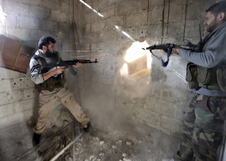 Fighters from the Free Syrian Army's Tahrir al Sham brigade fire back at Syrian army during heavy fighting in Mleha suburb of Damascus January 26, 2013. (Goran Tomasevic/Reuters)