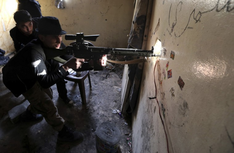 A Free Syrian Army fighter aims his rifle before opening fire at Syrian Army soldiers in the Arabeen neighborhood of Damascus January 18, 2013. (Goran Tomasevic/Reuters)